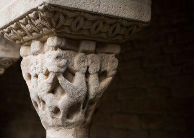 Típicas sirenas de cuerpo de animal alado y testa humana que se acoplan afrontadas en cada cara del capitel, acompañadas de cabezas de monstruos situadas en los ángulos que muerden los extremos de las alas.