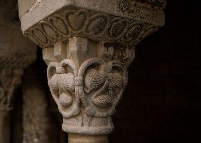 Entrelacement ovale lié par des feuilles et un trèfle avec un feuillage qui protège des cônes de pin.